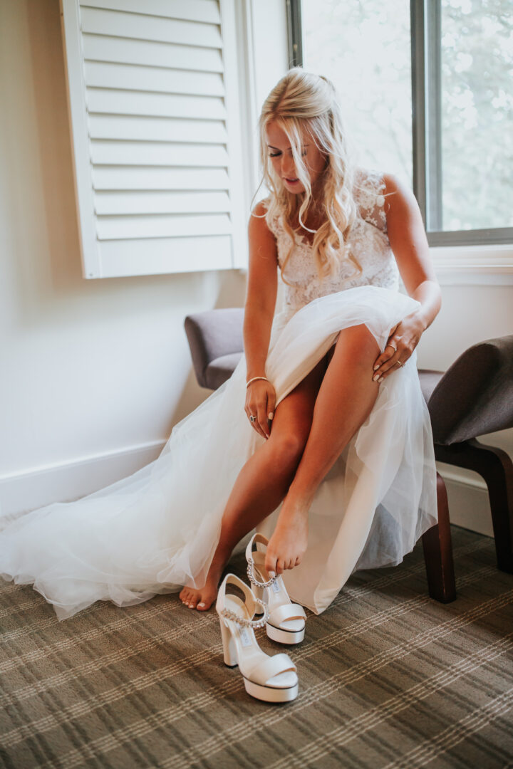 Bride putting on white Jimmy Choo shoes